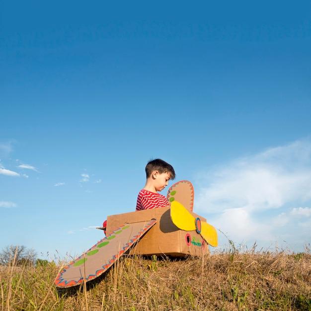 Kind im pappboot im freien