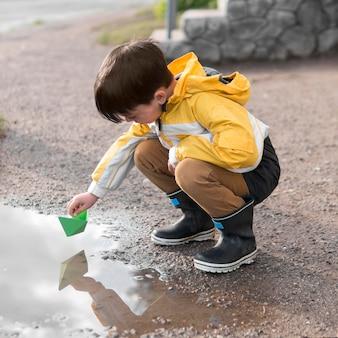 Kind im regenmantel, der im wasser spielt