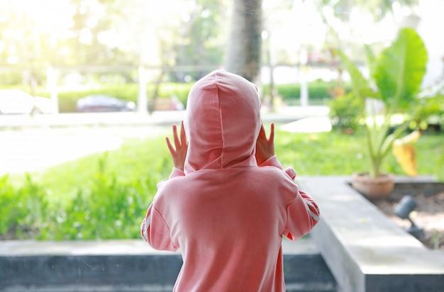 Kind im rosa trainingsanzug mit haube auf kopf an der hinteren ansicht des glasfensters, die heraus schaut, um den rasen im freien zu grünen.