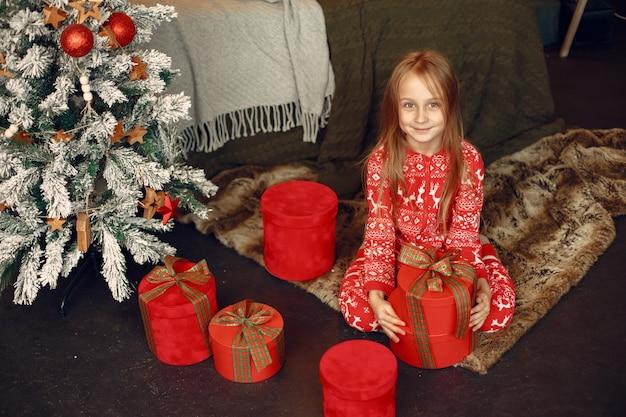 Kind im roten schlafanzug. tochter, die nahe weihnachtsbaum sitzt.