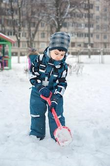 Kind im schnee mit einer schaufel