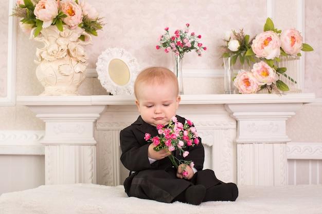 Kind im smoking sitzt auf dem bett neben dem kamin mit blumen in den händen.