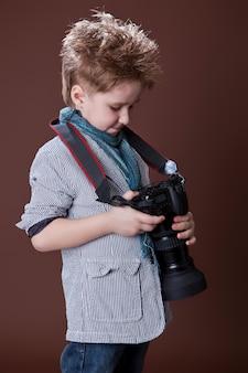 Kind im studio mit professioneller kamera. junge benutzt eine kamera auf braun.