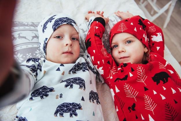 Kind im weichen warmen pyjama, der im bett spielt