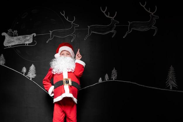 Kind im weihnachtsmannkostüm, das auf hintergrund zeigt