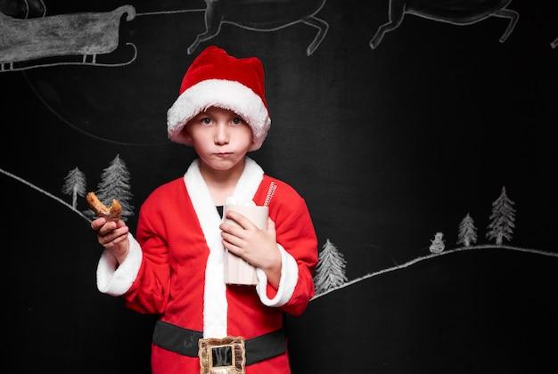 Kind im weihnachtsmannkostüm, das lebkuchen isst