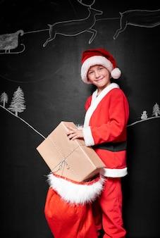 Kind im weihnachtsmannkostümkostüm, das geschenke verpackt