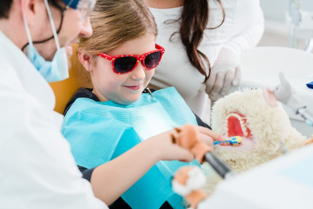 Kind im zahnarztbüro, das sich um zähne des haustierspielzeugs kümmert