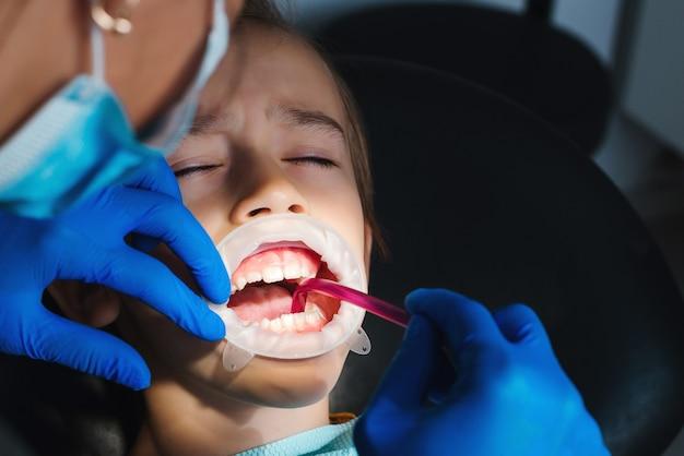 Kind in der klinik bei der zahnbehandlung. zahnarzt kieferorthopädie. ängstliches kind auf zahnarztstuhl.
