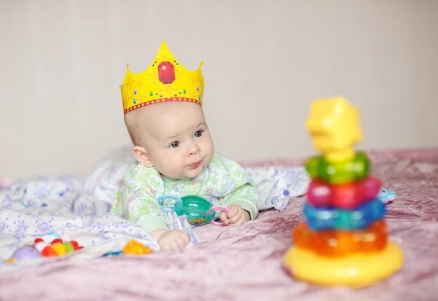 Kind in der krone liegt auf einem bett mit spielzeug