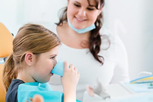 Kind in der zahnarztoperation, die zähne mit wasser spült