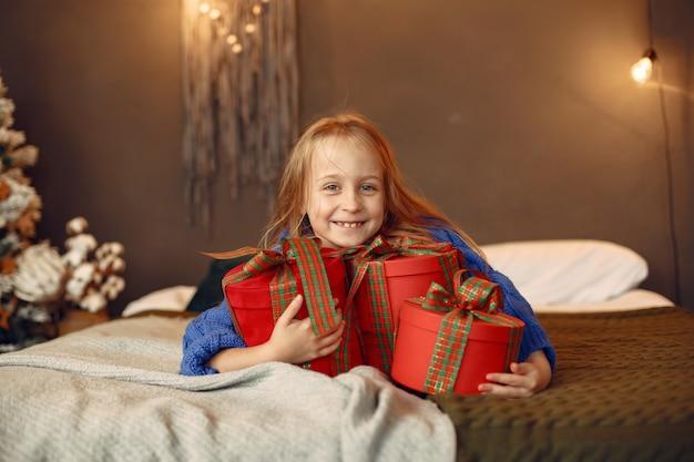 Kind in einem blauen pullover. tochter, die nahe weihnachtsbaum sitzt.