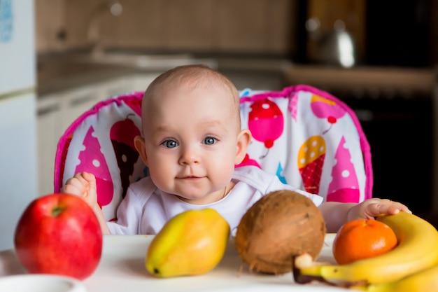Kind in einem hochstuhl obst essen und lächeln