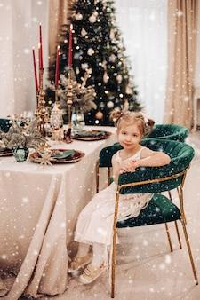 Kind in einem kleid, das es sich in einem grünen stuhl vor dem tisch bequem macht