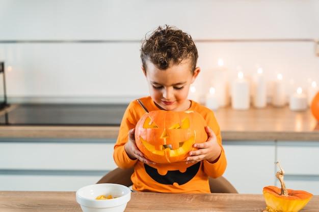 Kind in einem orangefarbenen kürbishemd, das seinen kürbis hält und betrachtet, der mit einem...