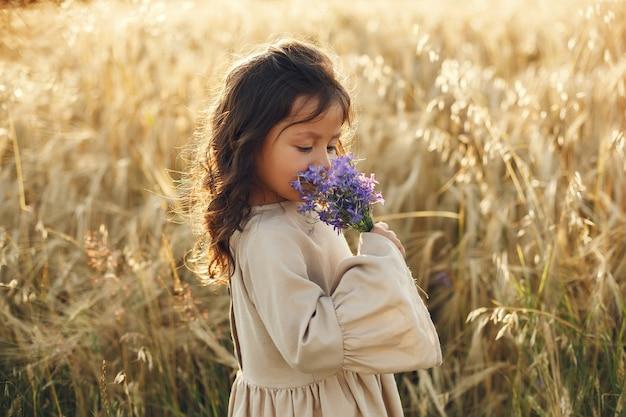 Kind in einem sommerfeld. kleines mädchen in einem niedlichen braunen kleid.