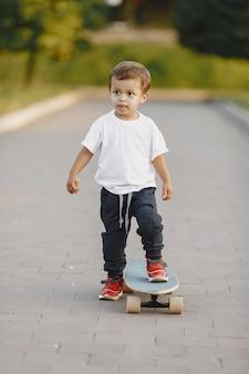Kind in einem sommerpark. junge in einem weißen t-shirt. kind mit schlittschuh.