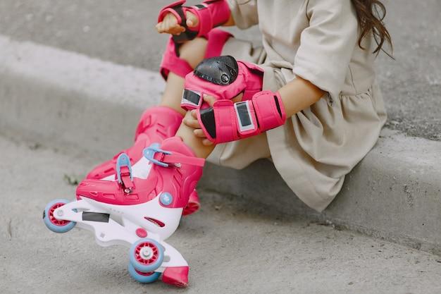 Kind in einem sommerpark. kind in einem rosa helm. kleines mädchen mit einer walze.