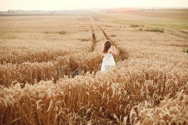 Kind in einem sommerweizenfeld. kleines mädchen in einem niedlichen weißen kleid.
