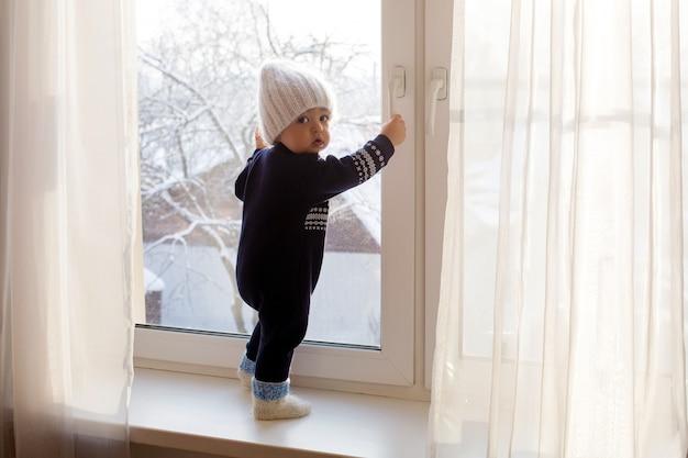 Kind in einem warmen blauen overall auf fenster im winter weiße strickmütze