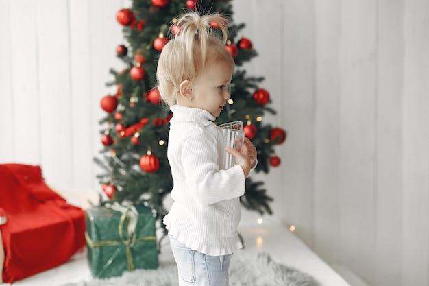 Kind in einem weißen pullover spielt. tochter steht in der nähe von weihnachtsbaum.