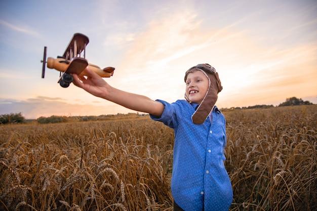 Kind in einem weizenfeld im dorf mit einem retro-flugzeug in seinen händen