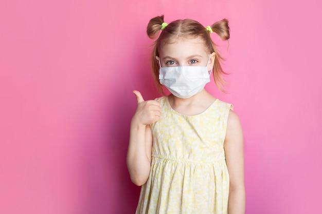 Kind in einer medizinischen maske auf einer rosa wand
