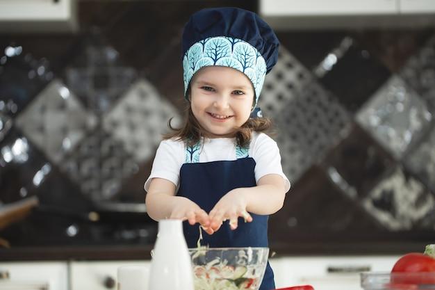 Kind in einer schürze und einer kochmütze rührt einen gemüsesalat in der küche