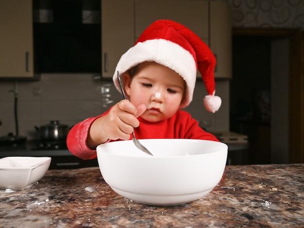 Kind in einer weihnachtsmütze, die ein neujahrsessen vorbereitet