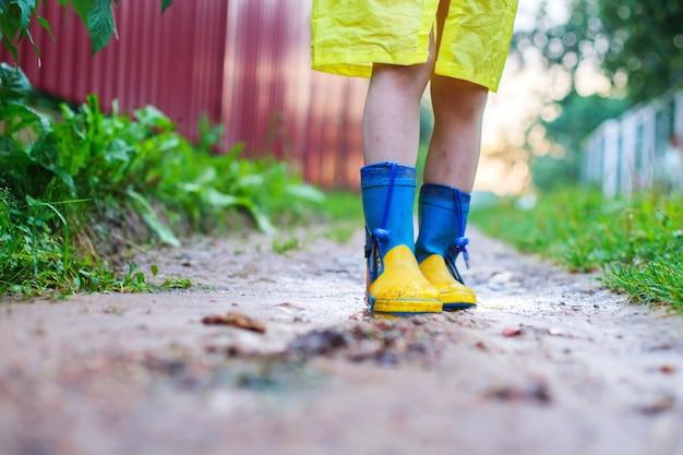Kind in gummistiefeln, das die füße des kindes in einem gummistiefel im freien geht