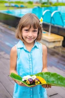 Kind in händen mit exotischen früchten. selektiver fokus.
