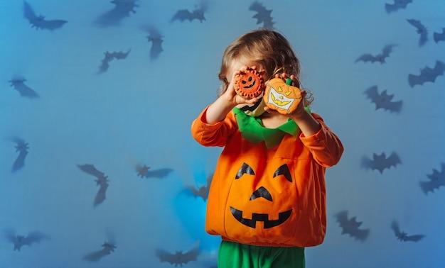 Kind in kürbiskarnevalskostüm und medizinischer maske, das mit keksen für halloween-party spielt