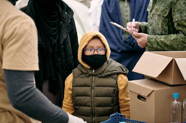 Kind in schutzmaske wartet auf das verteilen von kostenlosem essen