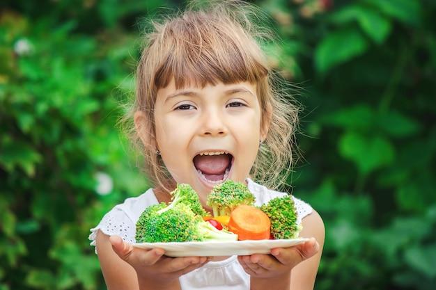 Kind isst gemüse. sommerfoto selektiver fokus