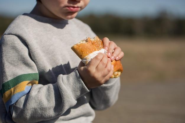 Kind isst sandwich im freien
