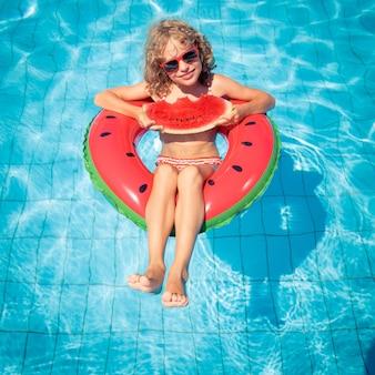 Kind isst wassermelone auf einer aufblasbaren wassermelone im schwimmbad