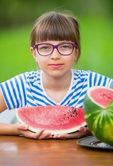 Kind isst wassermelonepre teen mädchen im garten hält ein stück wassermelone glückliches mädchen kind isst...