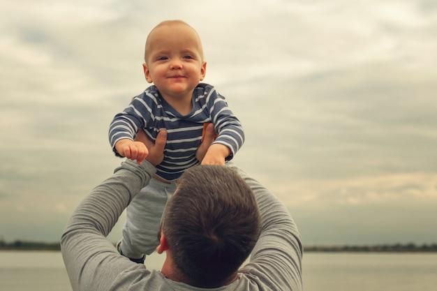 Kind ist in den armen des vaters. kind gegen den hintergrundhimmel auf händen des vatis.
