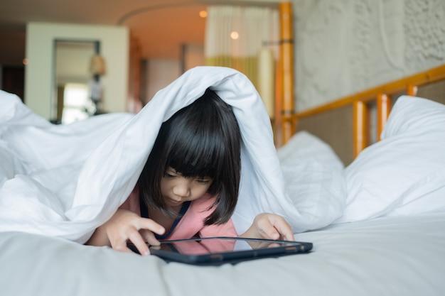 Kind ist süchtig nach tablet, kleines mädchen spielt smartphone, kind benutzt telefon, schaut cartoon