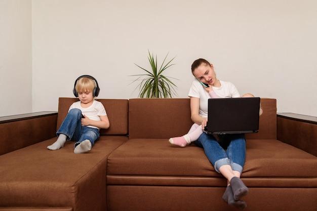 Kind junge benutzt telefon, während mutter mit laptop arbeitet. alleinerziehende mutter konzept
