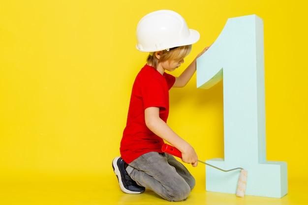 Kind junge blondes haar niedlich adrorable im roten t-shirt und im weißen helm, das zahlennummer auf gelb malt