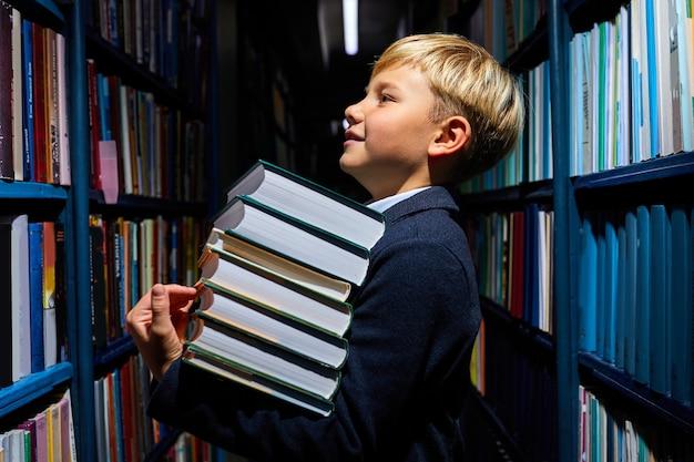 Kind junge hält stapel bücher in der bibliothek in der schule, bereitet sich auf die schulbildung vor, steht zwischen regalen