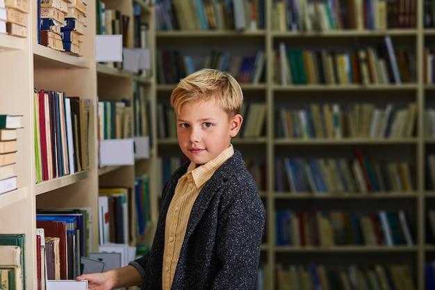 Kind junge in der bibliothek, kamera betrachtend. schuljunge steht zwischen regalen mit büchern