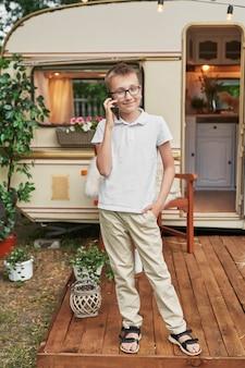 Kind junge mit einem telefon im urlaub im sommer in der nähe des hauses auf rädern