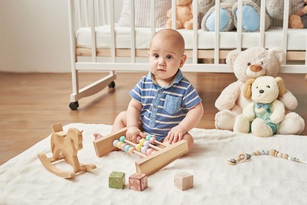 Kind junge spielt holzspielzeug in einem kinderzimmer in leuchtenden farben, skandinavischen stil kinderzimmer