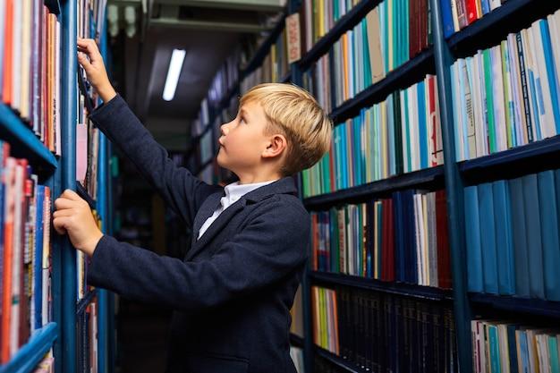 Kind junge sucht und wählt buch in buchhandlung, steht in der nähe von regalen, wird lernen und lernen. seitenansicht