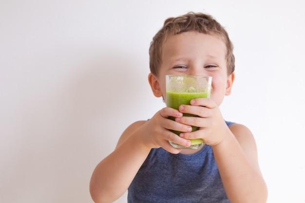 Kind (junge) trinkt gesunden grünen gemüsesmoothie - gesundes essen, veganes, vegetarisches, bio-lebensmittel- und getränkekonzept. sommergetränke.