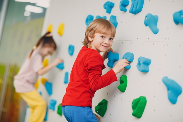 Kind kind junge an kletterwand kinder sport gesunden lebensstil im kindergarten oder sportzentrum in der schule