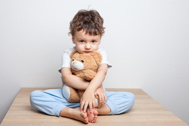 Kind, kleiner junge, der auf einem tisch sitzt, umarmt einen bären. ernsthafter blick in die kamera. müdigkeit und niedergeschlagenheit. weißer hintergrund. isoliert