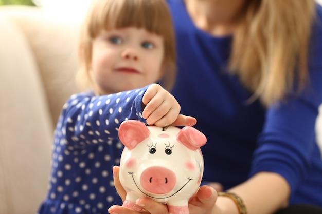 Kind kleines mädchen arm, das münzen in sparschwein setzt